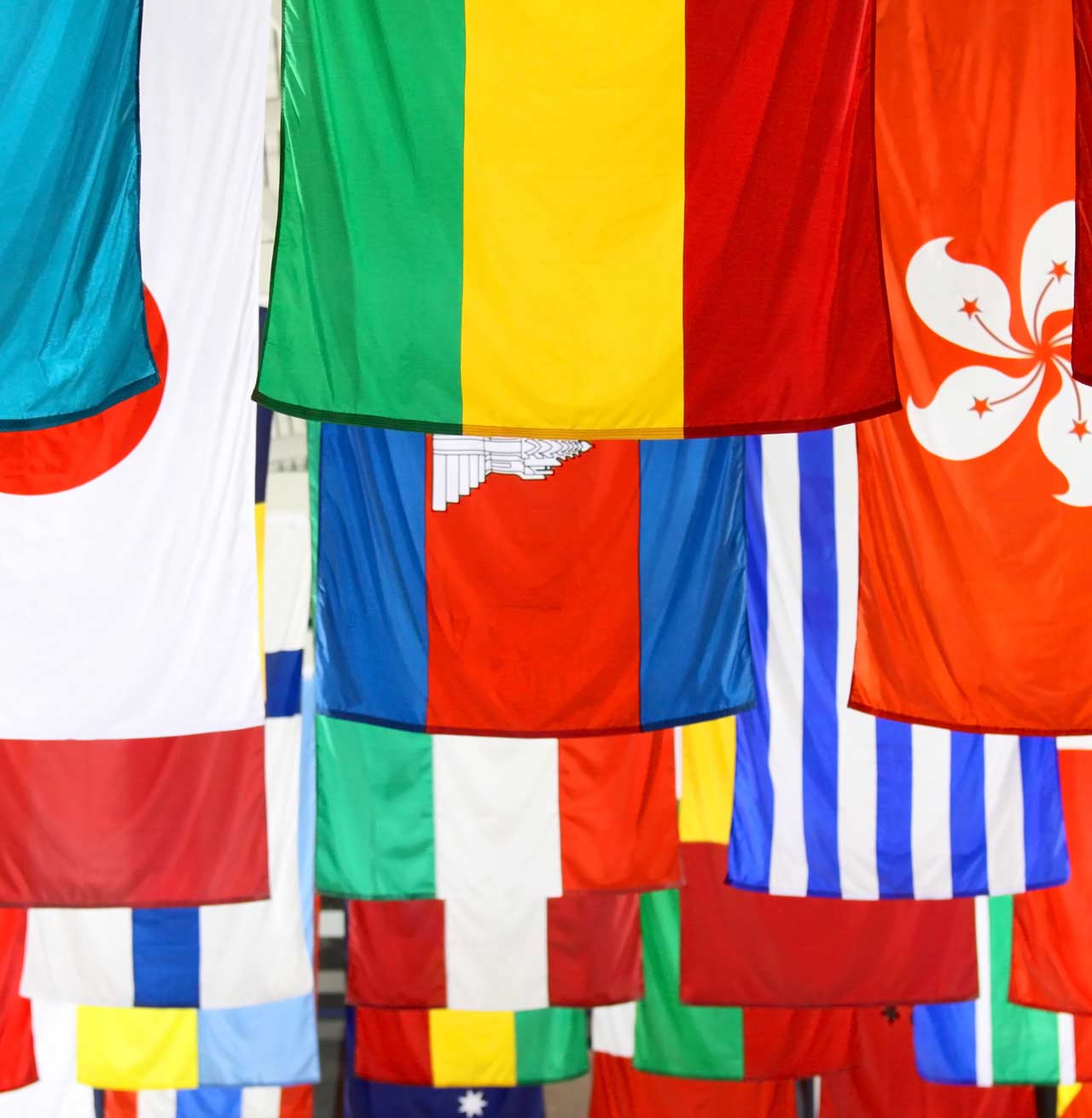 Flags representing different countries hanging from their short edge
