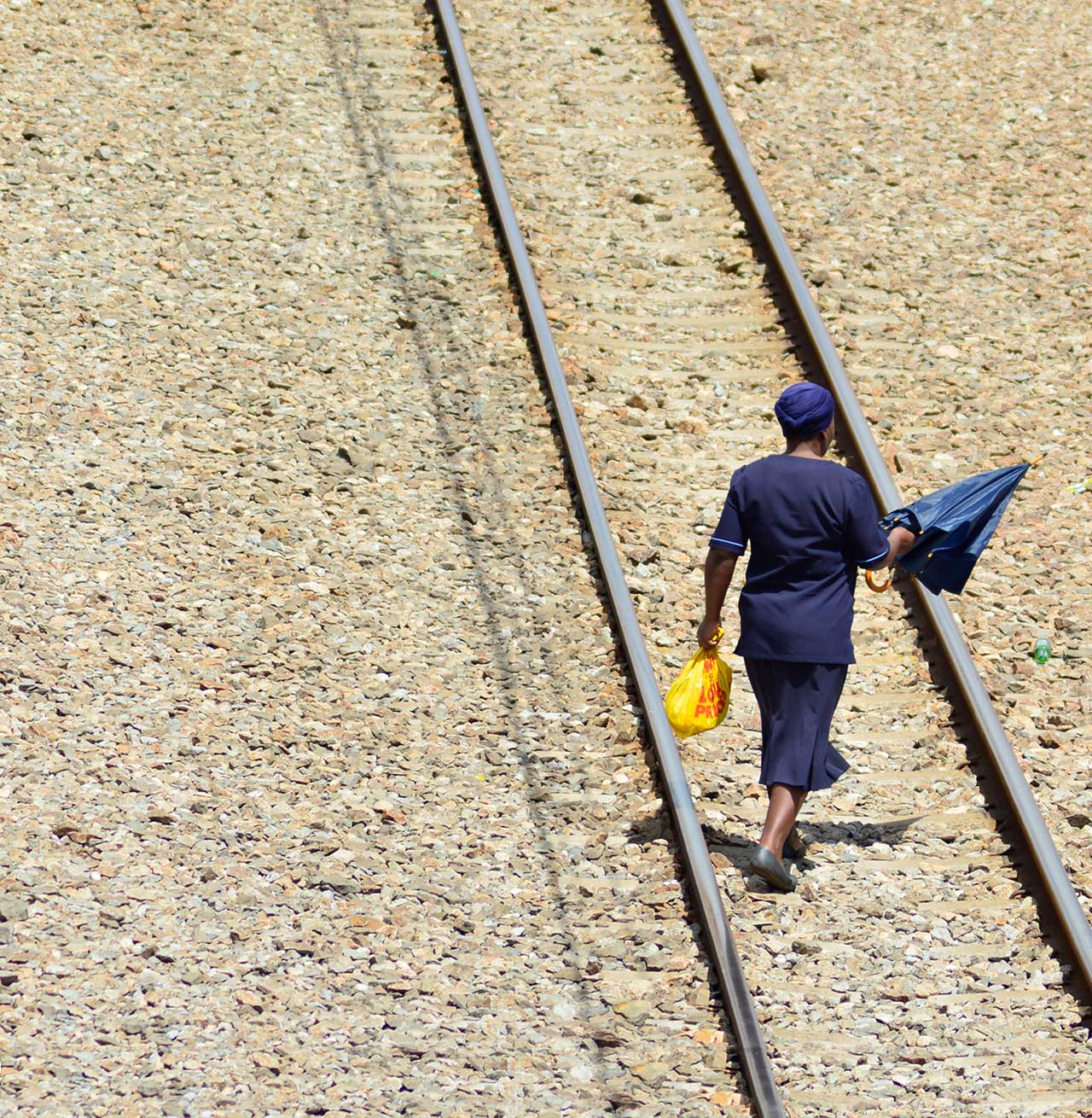 Person crossing train tracks in South Africa